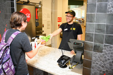 Male student employee serving a customer.