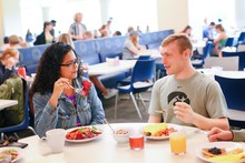 Male and female students eating together.