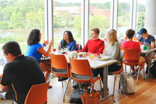 Group of students sitting and eating together.