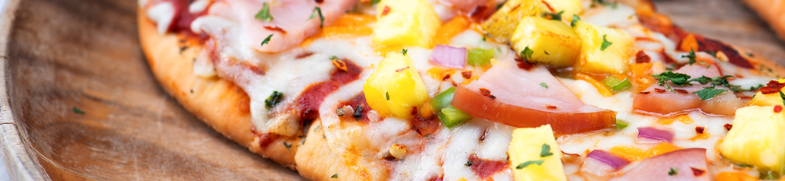 Pizza with cheese and pinapple on wooden block